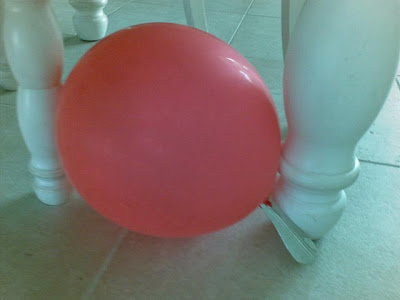 red balloon on floor by table