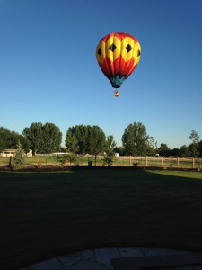 And THIS is what we woke up to Sunday morning! We heard a strange noise and went outside to see what it was... and it was a hot air balloon sailing right over the top of our house! It was really neat.