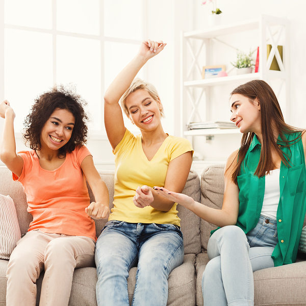 Happy female friends in colourful clothes having fun at home. Three young women laughing and dancing, slumber party, copy space